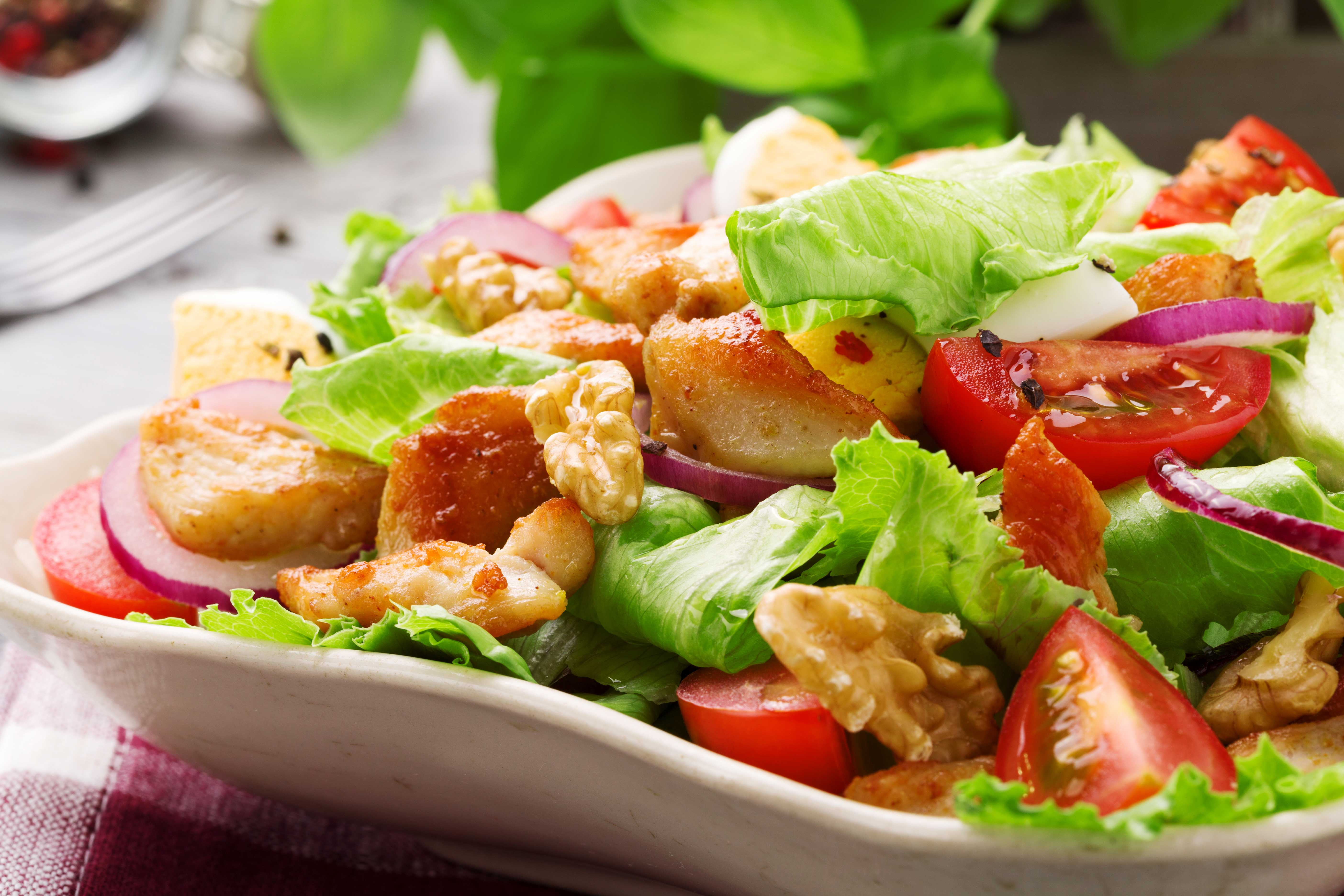 Delicious salad with chicken, nuts, egg and vegetables